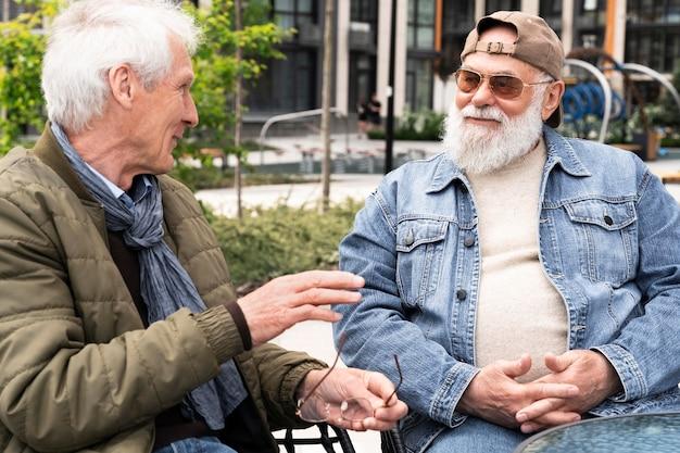Due uomini più anziani in città che chiacchierano insieme
