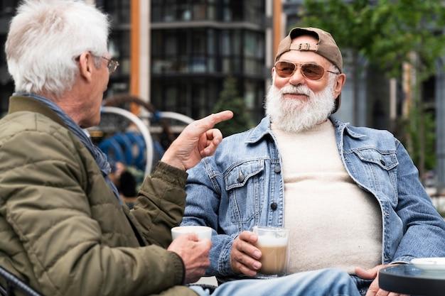 街で一緒にコーヒーを飲みながら談笑する 2 人の年配の男性