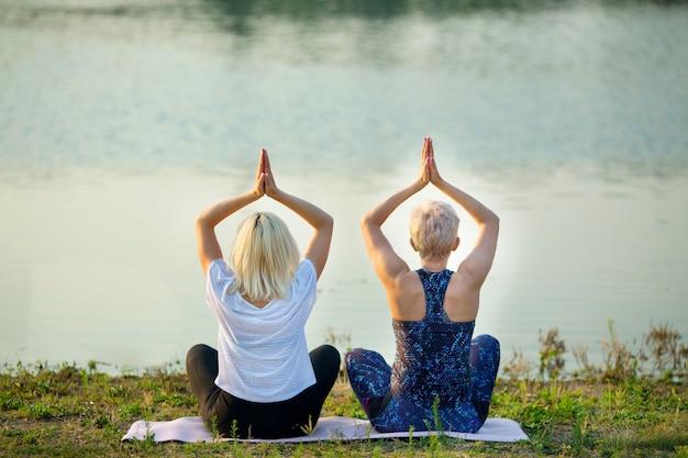夏に川の近くでヨガをしている2人の年上の女性