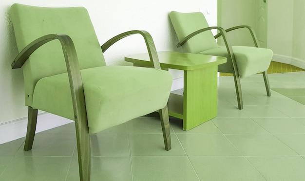 올리브색 안락의자 2개와 그 사이에 있는 녹색 커피 테이블이 벽 배경에 있으며, 현대적인 인테리어의 거실이나 호텔 홀이 있습니다.