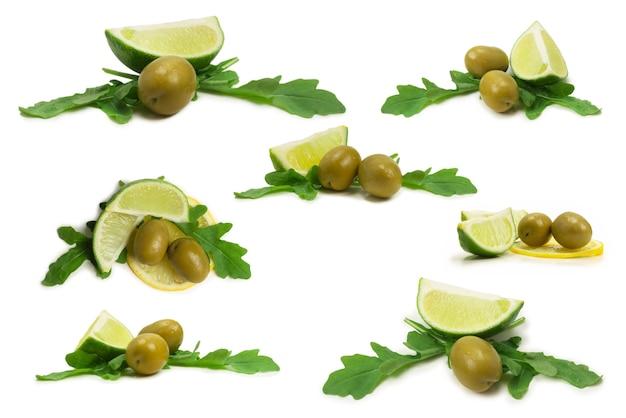 Две оливки, кусок лимона и листья рукколы, изолированные на белом фоне.