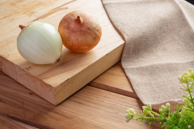 Two onions on a light brown wood cutting board.