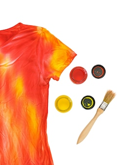 Two open cans of paint, a brush and a t-shirt in the style of tie dye. staining fabric in tie dye style.