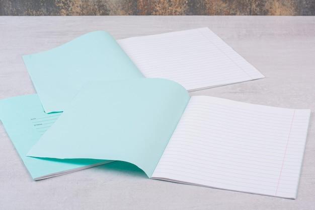 흰색 테이블에 두 개의 열린 카피북입니다.
