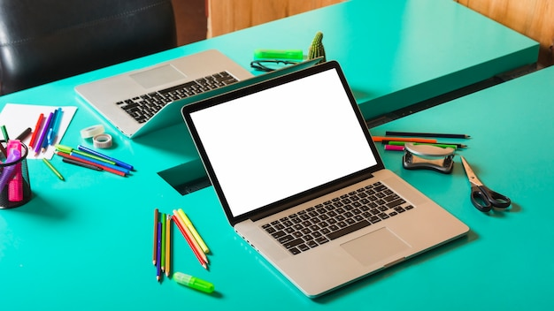 Two open laptop with colorful stationeries on turquoise table