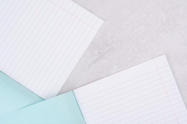 Две открытые тетради на белом.