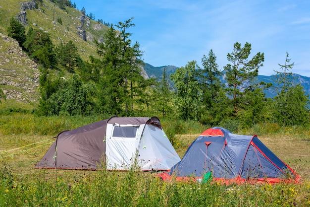 Две открытые палатки стоят на лугу с травой в горах. летнее солнце. склон горы и голубое небо на фоне. походный лагерь.