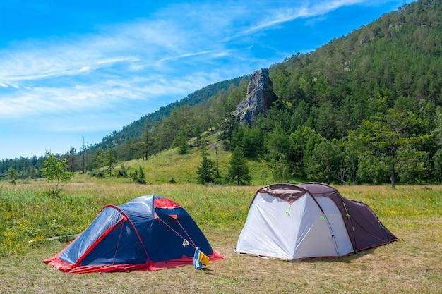 Две открытые палатки стоят на траве в горах. большой рок и голубое небо на фоне. походный лагерь.