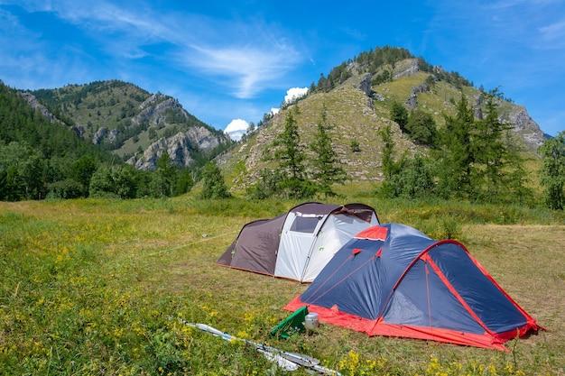 Две открытые палатки стоят на траве у гор. рядом весла с лодки. рафтинг-лагерь.