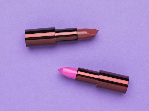 紫色のテーブルに口紅の2つの開いたチューブ。唇の装飾。フラットレイ。