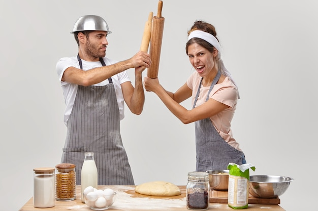Two opponents at kitchen. woman and man cooks struggle with kitchen utensils, compete who cooks better, make dough for baking pie, wear aprons, isolated over white wall. culinary battle