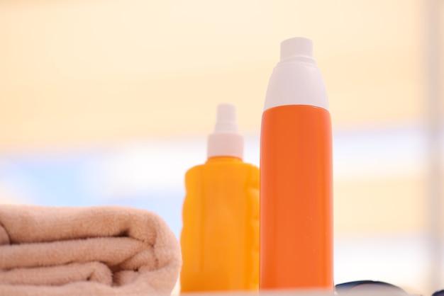 タオルのクローズアップの近くのビーチに横たわっている日焼け止めと2つのオレンジ色のボトル