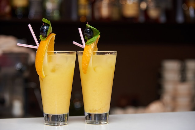 Two orange cocktails with a slice of orange, olive and mint.