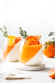 Two orange panna cotta desserts decorated with oranges stand on white