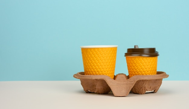 Two orange paper disposable cups stand in a brown tray on a blue background, no plastic, copy space