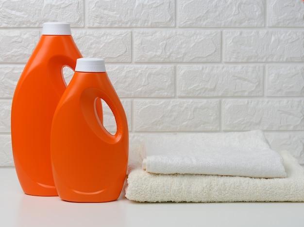 액체 세제 두 병과 흰색 선반에 수건 더미, 가정 세척