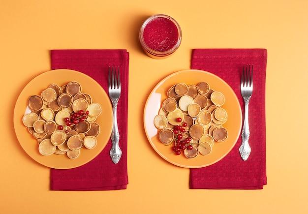 赤いナプキンの上にミニパンケーキが付いた2つのオレンジ色のプレートが立っています