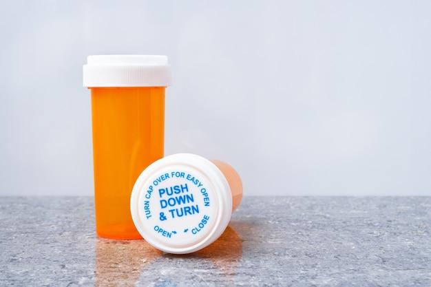 흰색 바탕에 광택있는 회색 표면에 안전 캡이있는 두 개의 오렌지 처방전 병, 한 병 서, 다른 거짓말