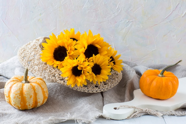 Two orange pumpkins and a bouquet of sunflowers in a straw hat on a bright wooden table