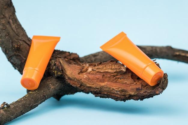 Две оранжевые трубки на ветке старого дерева на синем фоне.