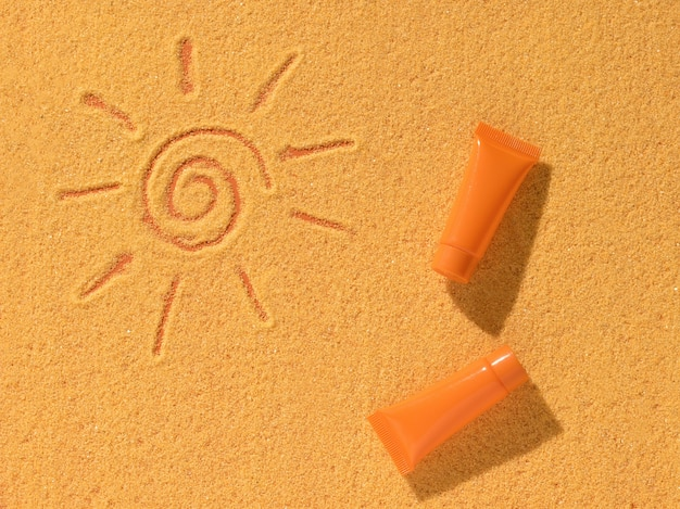 Two orange tubes of sunscreen and a sun painted on the sand. sun protection cream.