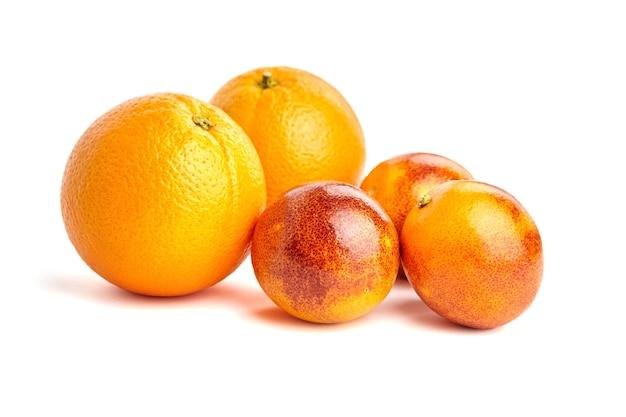 Два апельсина и три кровяных апельсина группируют целые цитрусовые, изолированные на белом фоне