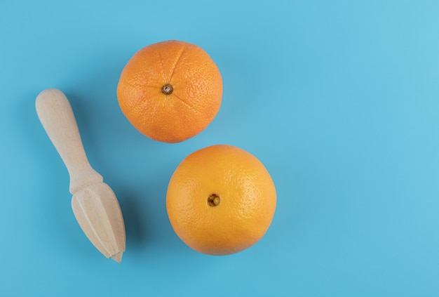 Two oranges and wooden reamer on blue table.