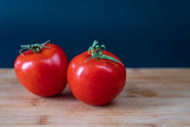 Два органических помидора на деревянном столе