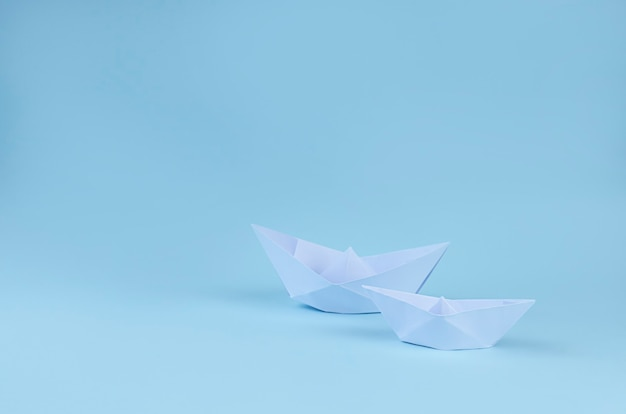 Two origami paper boats on light blue surface