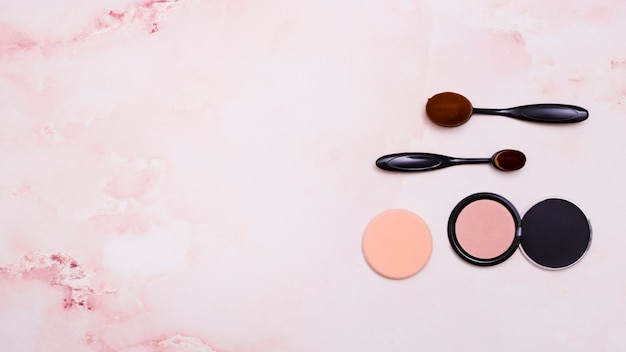 Two oval black brushes; compact face powder and puff on pink textured backdrop