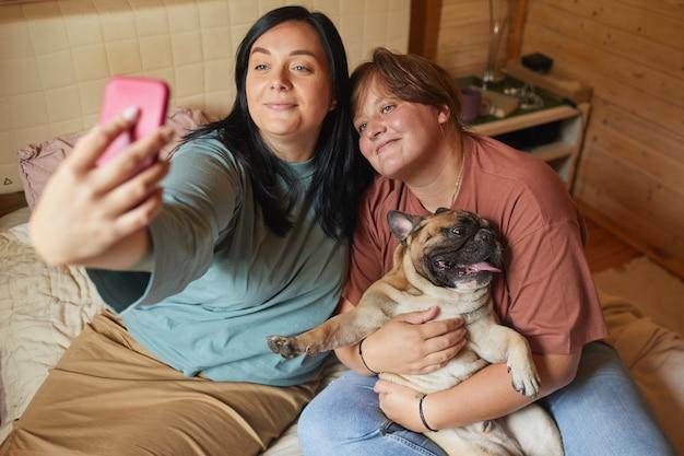 Две полные женщины сидят на кровати и делают селфи на мобильном телефоне со своим питомцем