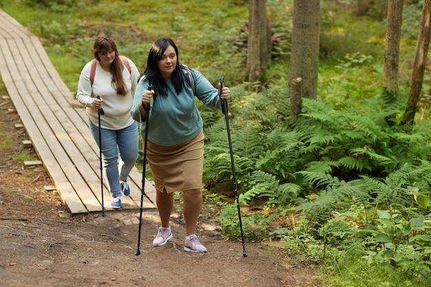 Две полные женщины ходят с палками в лесу во время спортивной ходьбы