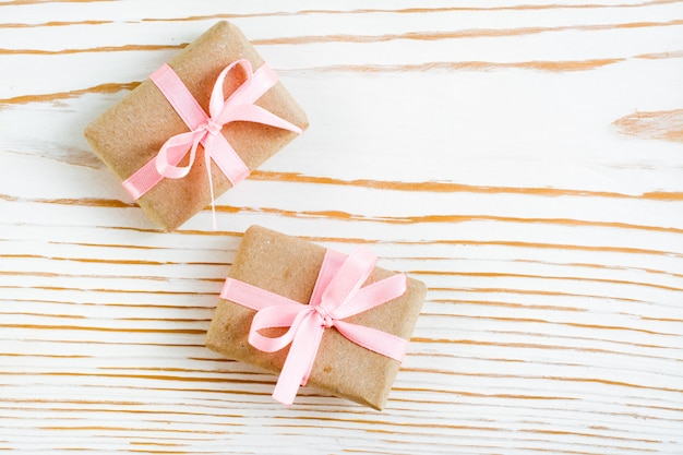 Two packaged gift with a pink ribbon on a white wood, top view