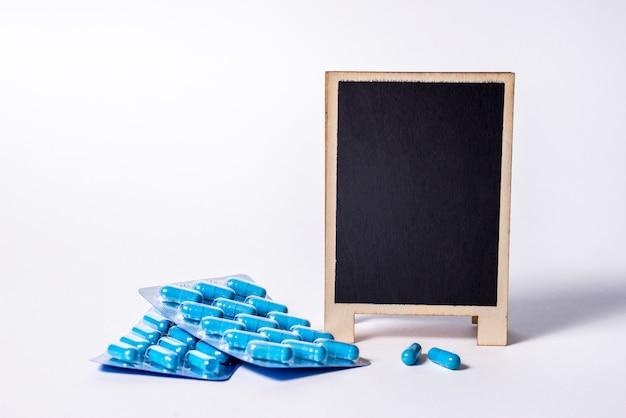 青いカプセルの2つのパッケージとテキスト用のスペースがある黒板。男性の健康と性エネルギーのための薬