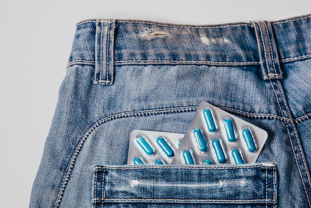 Две пачки синих капсул в кармане брюк. таблетки для мужского здоровья и сексуальной энергии в джинсах.