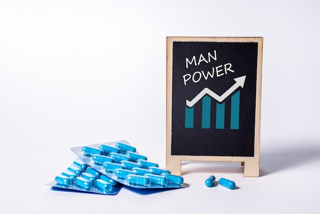 Two packs of blue capsules and the word man power on a chalkboard. pills for men's health and sexual energy. concept of erection, potency. treatment of male infertility and impotence.