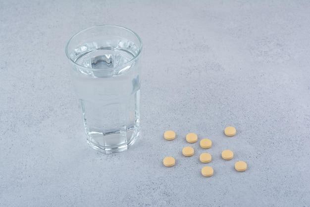 Due confezioni di pillole rosse con un bicchiere d'acqua.