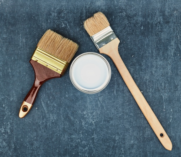 Two paint brushes and a closed can with white paint