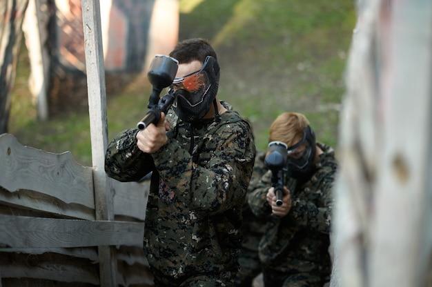 Два игрока в пейнтбол прицеливаются из оружия из приюта на детской площадке