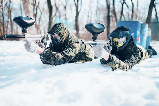 Two paintball players lies on the snow and shooting at the enemy in winter forest battle. extreme sport game