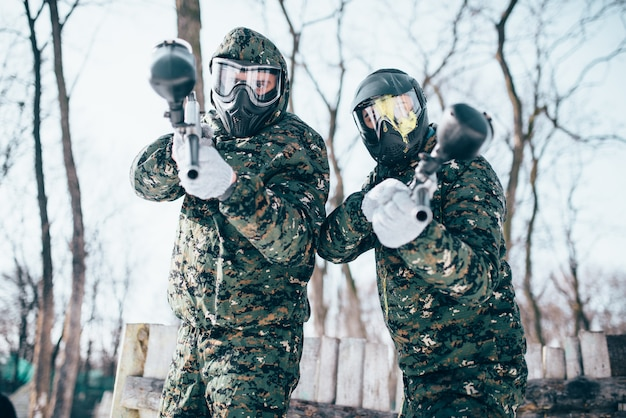 Two paintball players in splattered masks, team poses after winter battle. extreme sport game, soldiers in special uniform, paintballing