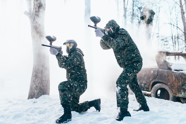 Two paintball players in uniform and masks shooting at the enemy, side view, winter forest battle. extreme sport game