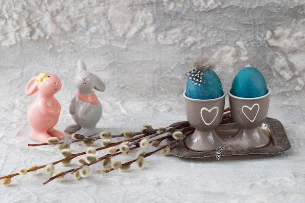 Two painted eggs on a stand on a silver old tray, feathers, a willow and two bunnies nearby