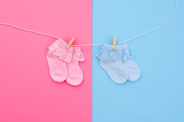 青とピンクの背景の物干しにぶら下がっている2つのペアの青とピンクのかわいいベビーソックス。ベビーアクセサリー。フラットレイ。