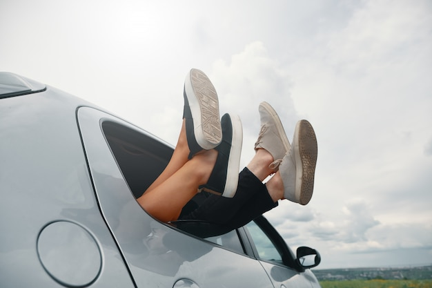 Two pair of legs wearing sneakers out the car window