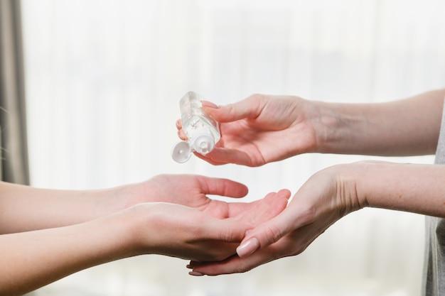 두 쌍의 여성 손은 코로나바이러스 세계 전염병 동안 바이러스, 미생물, 가족 돌봄 개념에서 팔을 청소하기 위해 방부제를 사용합니다.