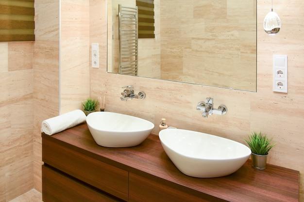 Две парные белые раковины в современном интерьере ванной комнаты.