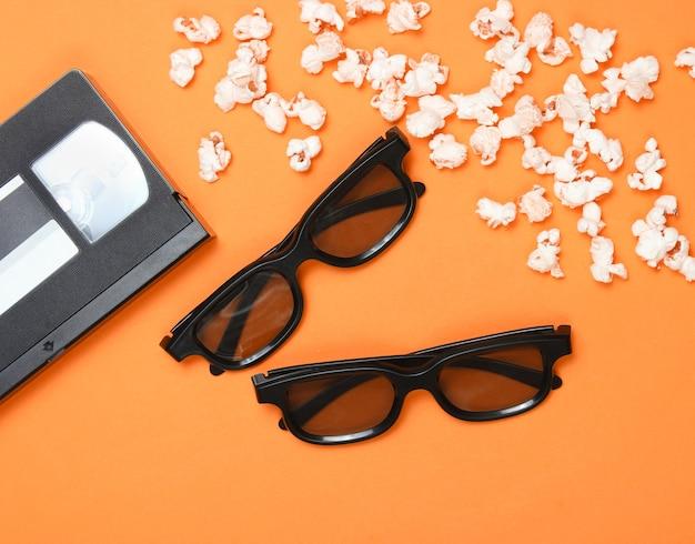 오렌지 배경에 두 쌍의 3d 안경, 팝콘, 비디오 카세트