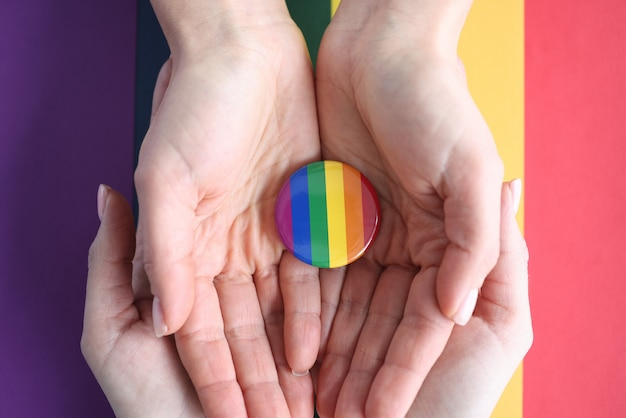Two pairs of female hands holding lgbt symbol on surface of flag closeup