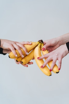 Two pairs of hands holding a few bananas